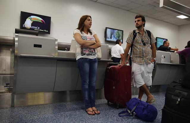 MIAMI, FL - APRIL 16: An American Airlines passenger Luciara Miranda (L) and Tiago Oliveira wait to be helped at the ticket counter at Miami International Airport on April 16, 2013 in Miami, Florida. Thousands of American Airlines travelers became stranded today when the airline was forced to ground all its flights after a nationwide problem with its computer systems (Photo by Joe Raedle/Getty Images)