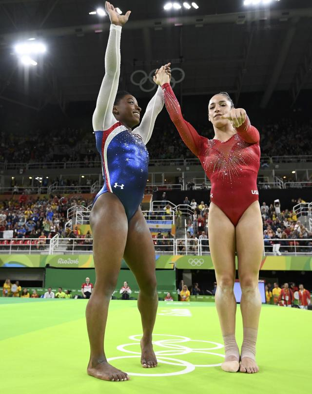 2016 Rio Olympics - Artistic Gymnastics - Final - Women's Individual All-Around Final - Rio Olympic Arena - Rio de Janeiro, Brazil - 11/08/2016. Silver medal winner Alexandra Raisman (USA) of the U.S. and gold medal winner Simone Biles (USA) of the U.S. point at photographers as they celebrate. REUTERS/Dylan Martinez FOR EDITORIAL USE ONLY. NOT FOR SALE FOR MARKETING OR ADVERTISING CAMPAIGNS.