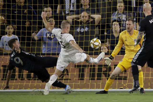 Colorado Rapids defender Tommy Smith (5) kicks the ball into his own goal to score a Sporting Kansas City goal while trying to defend against Sporting Kansas City forward Krisztian Nemeth (9) during the first half of an MLS soccer match Saturday, Sept. 21, 2019, in Kansas City, Kan. (AP Photo/Charlie Riedel)