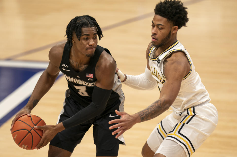 Providence's David Duke, left, looks to make his move against Villanova's Justin Moore, right, during the first half of an NCAA college basketball game Saturday, Jan. 23, 2021, in Villanova, Pa. (AP Photo/Chris Szagola)