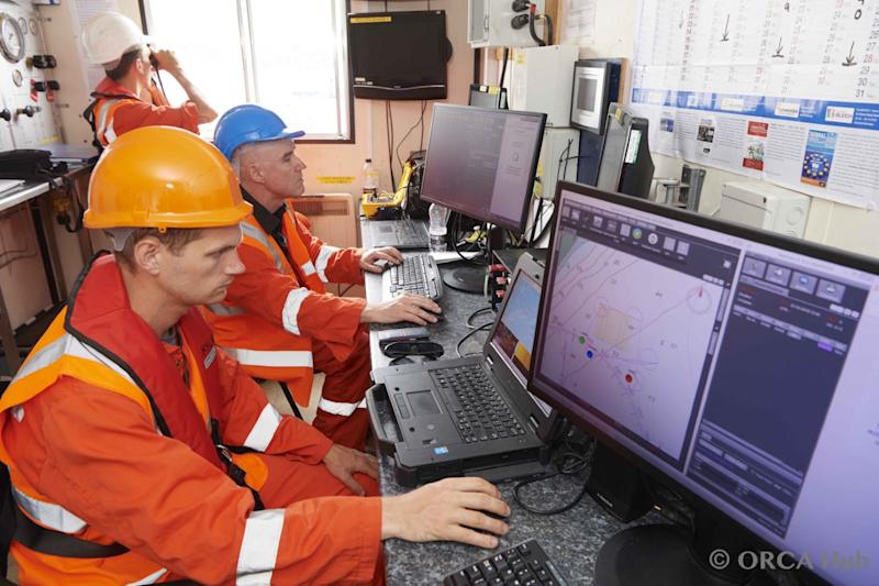 Offhshore workers at computer