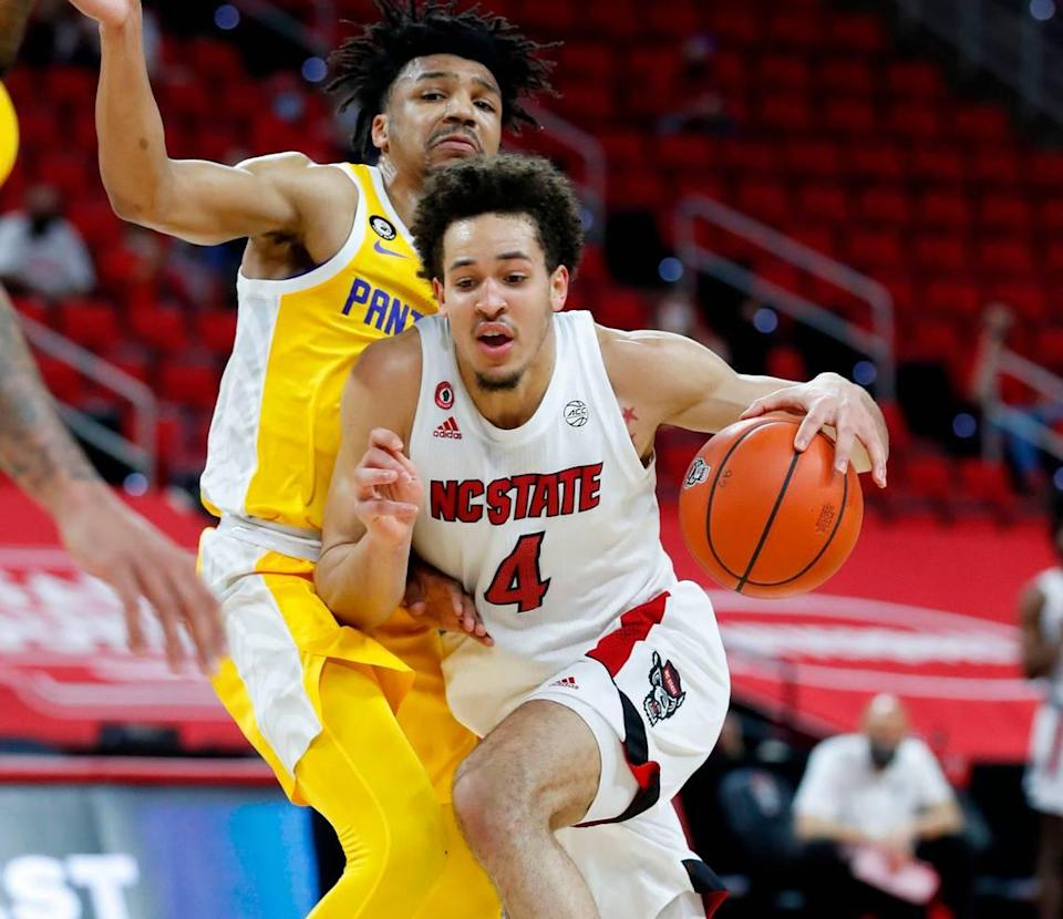 N.C. State's Jericole Hellems (4) drives by Pittsburgh's Ithiel Horton (0) during the first half of N.C. State's game against Pittsburgh at PNC Arena in Raleigh, N.C., Sunday, February 28, 2021.
