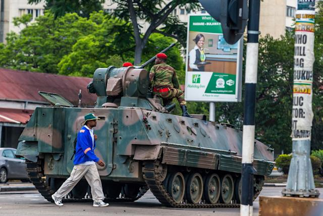 A man walks past an armored personnel carrier stationed at an intersection in Harare as Zimbabwean soldiers regulate traffic on Nov. 15, 2017.