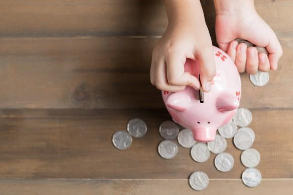 A child puts a coin in a pink piggy bank with other coins scattered around a tabletop.