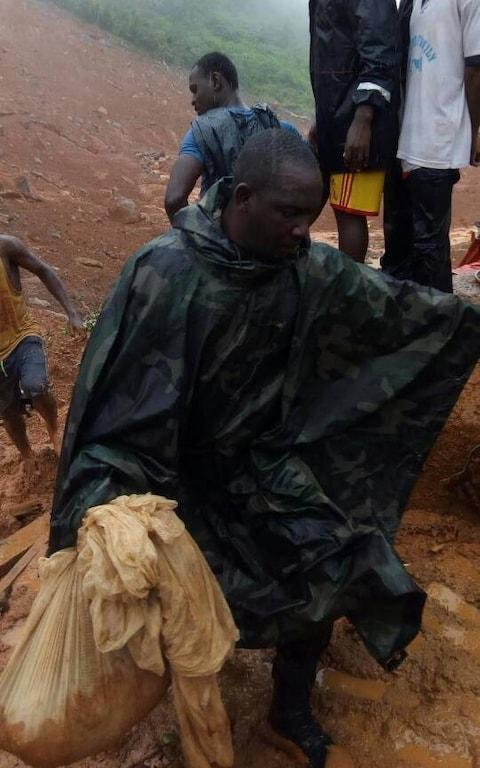 <span>Locals carry belongings after the mudslide early on Monday in this picture said to show the scene near Freetown</span> <span>Credit: Society for Climate Change Communication Sierra Leone </span>