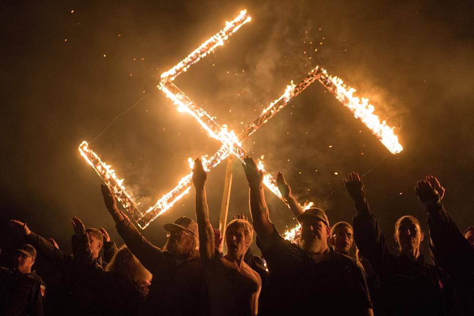 Supporters of the National Socialist Movement, a white nationalist political group, give Nazi salutes while taking part in a swastika burning at an undisclosed location in Georgia, U.S. on April 21, 2018. (Go Nakamura/Reuters)
