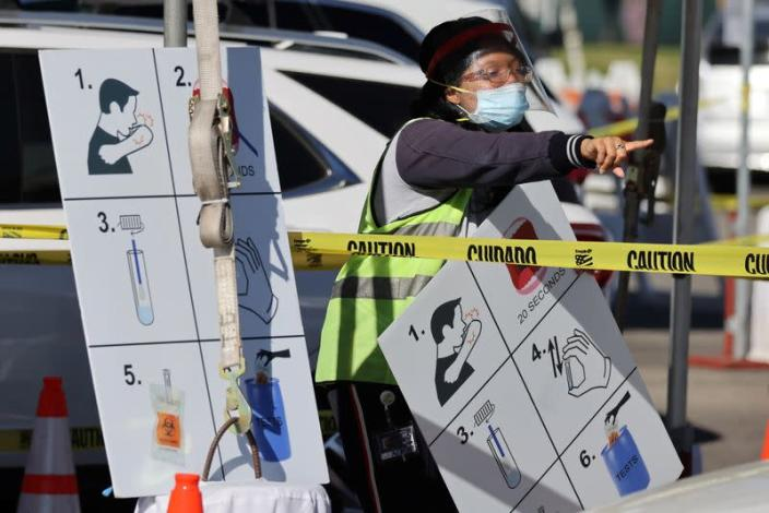 A worker gives instructions to drivers in line for novel coronavirus tests in Los Angeles
