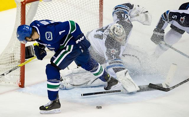 Vancouver Canucks' David Booth, left, loses control of the puck on a scoring chance on Winnipeg Jets' goalie Ondrej Pavelec, of Czech Republic, during the third period of an NHL hockey game in Vancouver, British Columbia, on Sunday, Dec. 22, 2013. (AP Photo/The Canadian Press, Darryl Dyck)