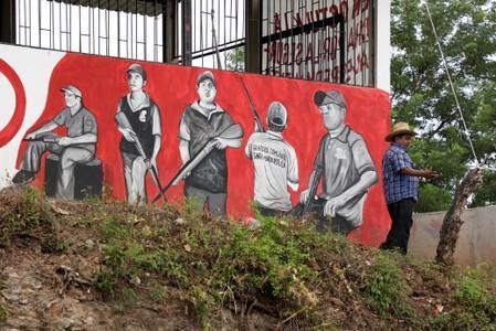 A member of the Community Police is seen next to mural at a checkpoint in the municipality of San Diego Xayakalan