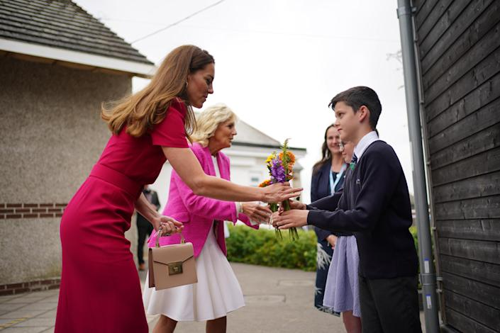 Catherine, Duchess of Cambridge and First lady Dr. Jill Biden are presented with flowers by the head boy and head girl during a visit to Connor Downs Academy on June 11, 2021. / Credit: Aaron Chown / Getty Images