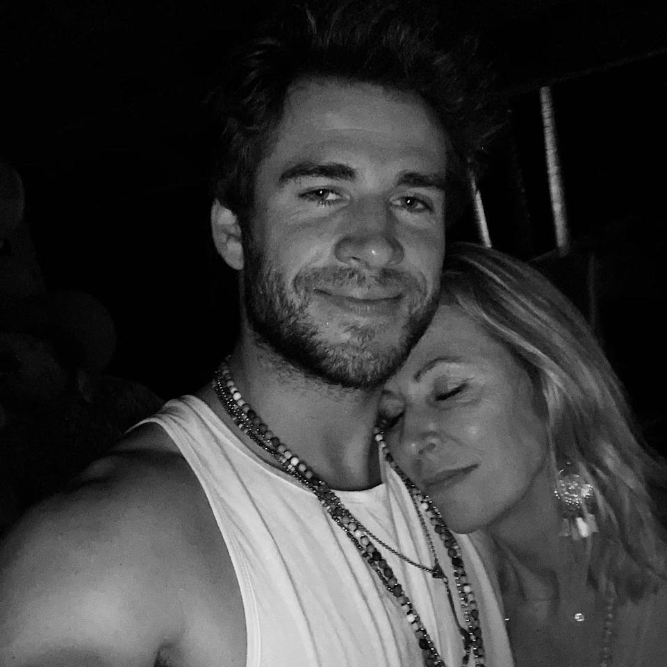 Liam Hemsworth smiling at the camera with his mum resting on his shoulder