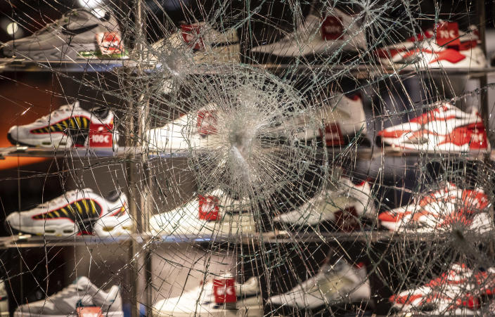 A window of a shop for shoes is destroyed at the Koenigstrasse in Stuttgart, Germany, Sunday, June 21, 2020. Dozens of violent small groups devastated downtown Stuttgart on Sunday night and injured several police officers, German news agency DPA reported. (Christoph Schmidt/dpa via AP)