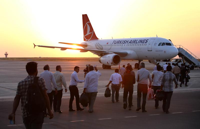 Some of the thirty-two Turkish truck drivers, held hostage for three weeks by Islamic militants in Iraq, on the tarmac before flying to Ankara after their release on July 3, 2014 at Arbil's airport (AFP Photo/Safin Hamed)