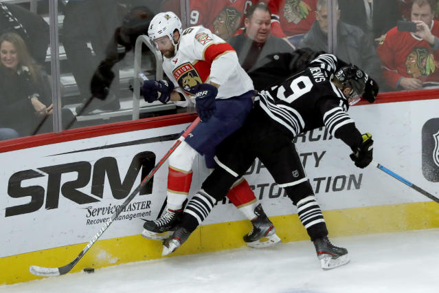 Chicago Blackhawks' Jonathan Toews (19) checks Florida Panthers' Aaron Ekblad against the boards during the first period of an NHL hockey game Tuesday, Jan. 21, 2020, in Chicago. (AP Photo/Charles Rex Arbogast)