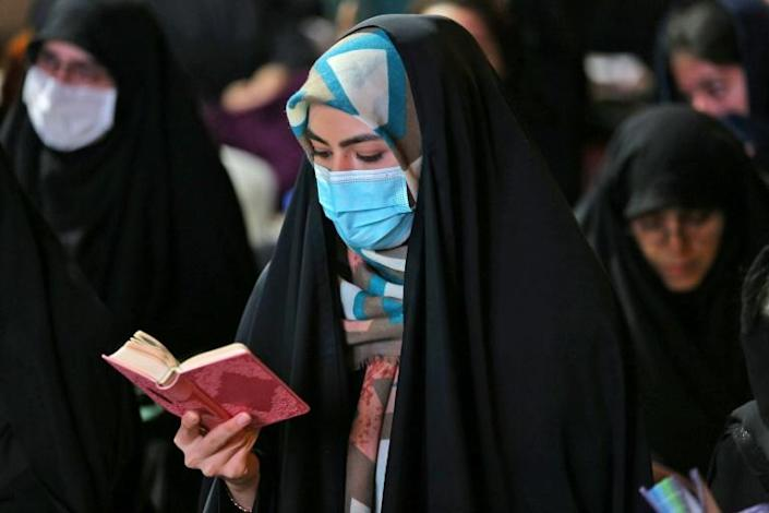 An Iranian woman wearing a face mask attends Laylat al-Qadr prayers, one of the holiest nights during the Muslim fasting month of Ramadan, outside a mosque in the Tehran, on May 13, 2020 (AFP Photo/ATTA KENARE)