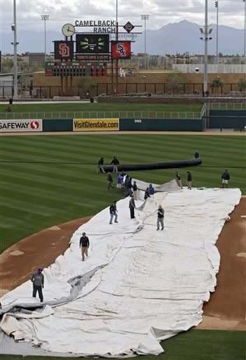 The grounds crew removes the tarp before an exhibition spring training baseball game between the San Diego Padres and Chicago White Sox Friday, March 8, 2013, in Glendale, Ariz. (AP Photo/Mark Duncan)