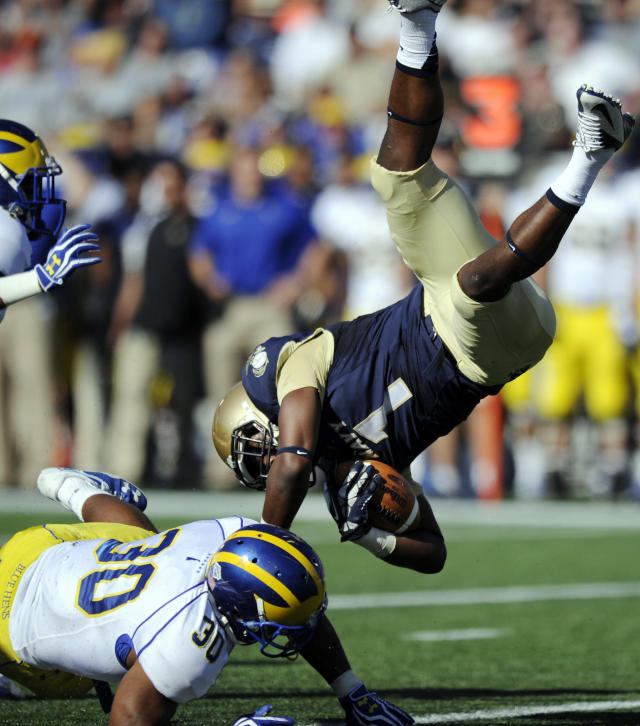 Navy cornerback Brendon Clements (1) goes airborne after he was tackled by Delaware running back Andrew Pierce (30) after he intercepted a pass during the first half of an NCAA college football game, Saturday, Sept. 14, 2013, in Annapolis, Md. Also seen is Delaware wide receiver Jerel Harrison. (AP Photo/Nick Wass)
