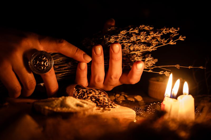 In the hands of the witches bunch of dry herbs for divination. The light from the candles on the old magic table. Attributes of occultism and magic.