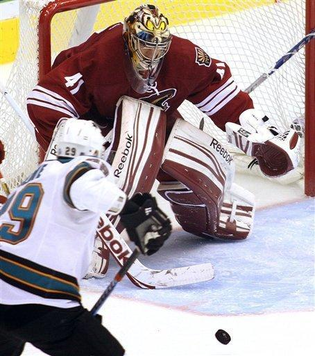 Phoenix Coyotes' goalie Mike Smith (41) keeps an eye on the puck as San Jose Sharks' Ryane Clowe vies for the puck during the third period of their NHL hockey game Saturday, Feb, 4, 2012 in Glendale, Ariz. (AP Photo/Darryl Webb)