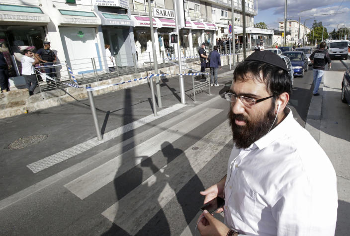 A member of the Jewish community who did not give his name, walks near the kosher grocery store where a bomb exploded in Sarcelles, north of Paris, Wednesday, Sept. 19, 2012. Four people where injured when a small package bomb exploded inside a kosher grocery store in Sarcelles a Paris suburb. (AP Photo/Michel Euler)