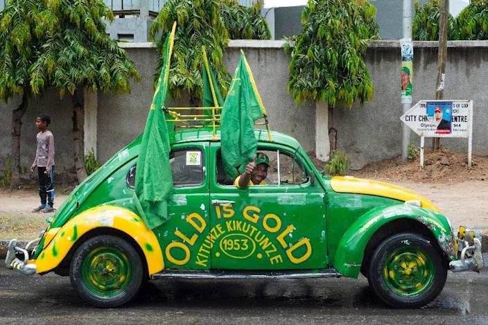 A man gives a thumbs-up from a Volkswagen Beetle after the official ceremony to announce the victory of the Tanzanian president-elect after presidential elections in Dar es Salaam October 30, 2015 (AFP Photo/Daniel Hayduk)