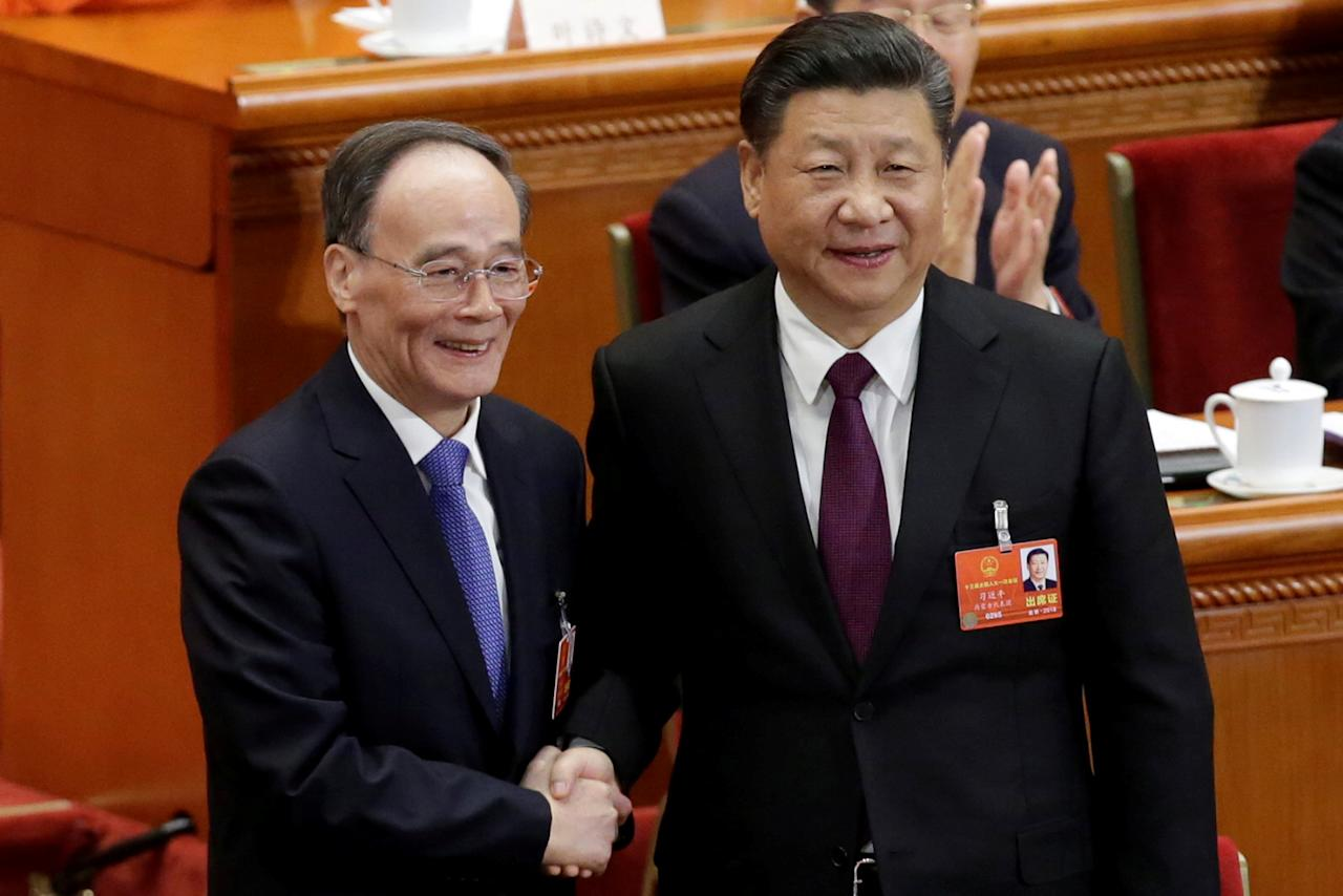 Chinese President Xi Jinping (R) shakes hands with newly elected Chinese Vice President Wang Qishan at the fifth plenary session of the National People's Congress (NPC) at the Great Hall of the People in Beijing, China March 17, 2018.  REUTERS/Jason Lee     TPX IMAGES OF THE DAY