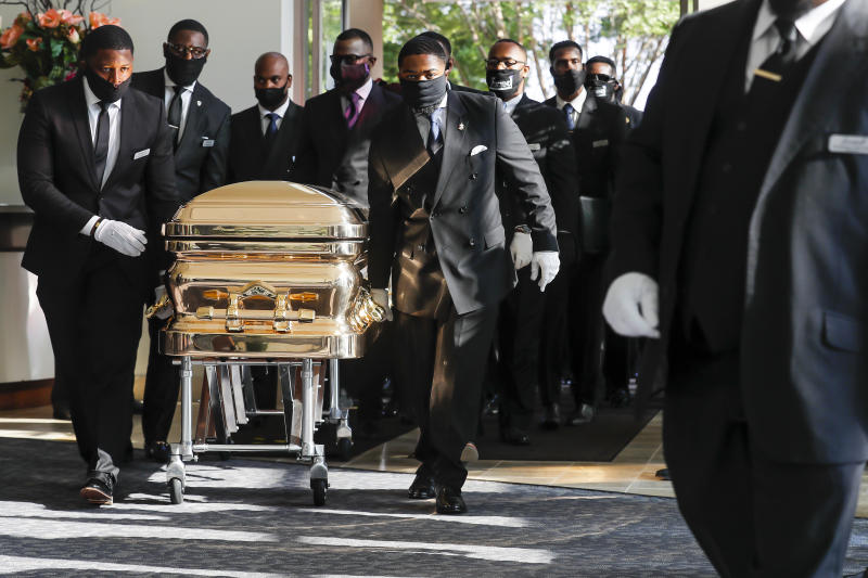Pallbearers bring the casket into the church for the funeral for George Floyd