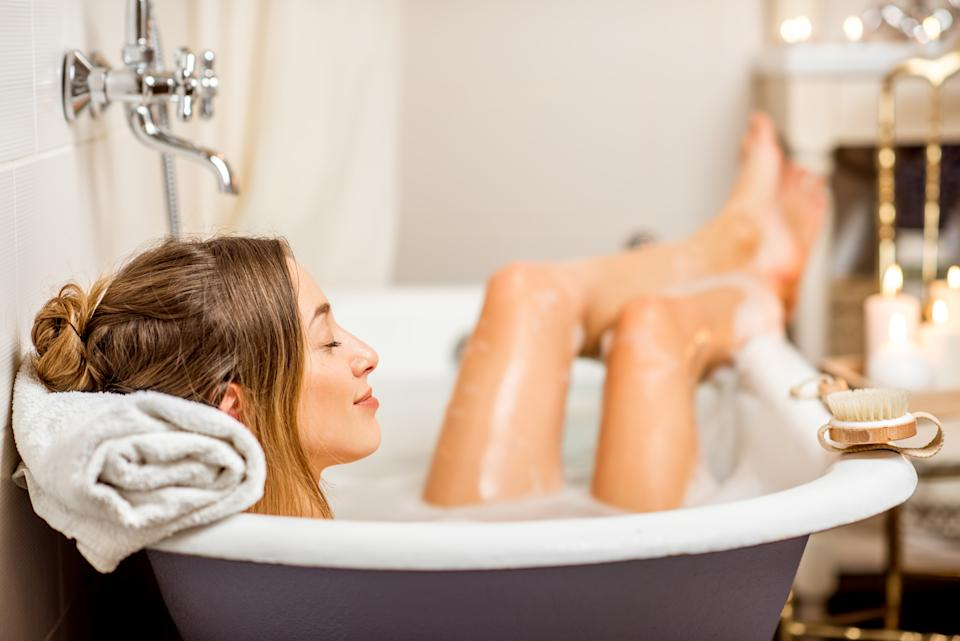 Young woman relaxing in the beautiful vintage bath full of foam in the retro bathroom decorated with candles