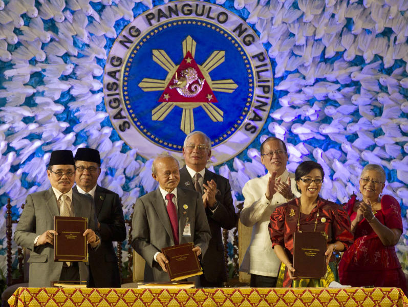 In this handout photo released by the Malacanang Photo Bureau, President Benigno S. Aquino III, third from right, applauds with Moro Islamic Liberation Front (MILF) Chairman, Al Haj Murad Ebrahim, second from left, Malaysian Prime Minister Najib Razak, center, and Secretary Teresita Quintos-Deles, Presidential Adviser on the Peace Process, right, after the signing of the Comprehensive Agreement on the Bangsamoro (CAB) by MILF chief negotiator Mohagher Iqbal, left, Datu Tengku Gnafar, third from left, and Miriam Coronel Ferrer, second from right, of the Philippine government in a ceremony at the Malacanang Presidential Palace in Manila, Philippines Thursday March 27, 2014. The Philippine government signed a peace accord with the country's largest Muslim rebel group on Thursday, the culmination of years of negotiations and a significant political achievement for President Aquino.(AP Photo/Malacanang Photo Bureau, Ryan Lim)