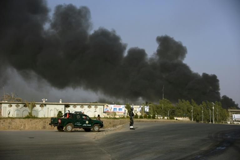 Afghan police arrive near a site of car bomb attack as smoke rises from the Police headquarters in Kandahar province on July 18, 2019.  At least 11 people were killed and scores more wounded when the Taliban attacked a police headquarters in the southern city of Kandahar, officials and the insurgents say