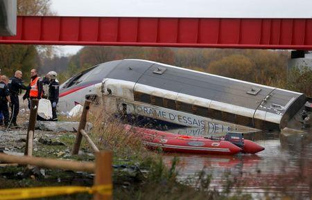 Rescue workers search the wreckage of a test TGV train that derailed and crashed in a canal outside Eckwersheim near Strasbourg