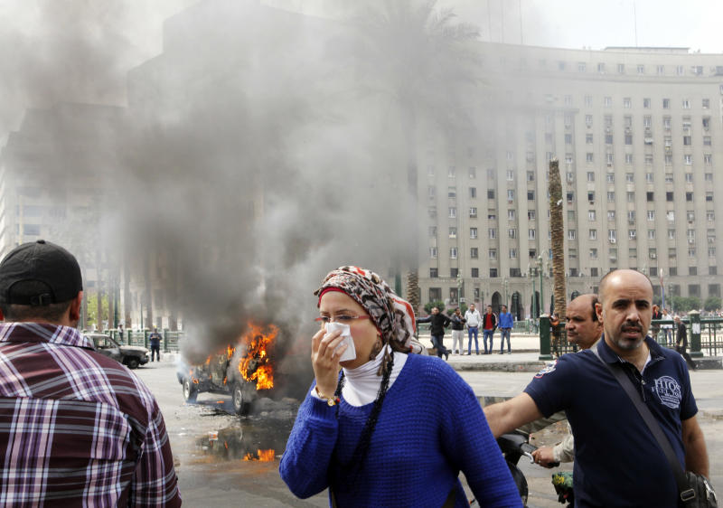 An Egyptian covers her face as she passes by a burning police vehicle, which has been set afire by angry protesters in Tahrir Square, once the epicenter of protests against former President Mubarak, in Cairo, Egypt, Monday, March 18, 2013. Egypt is currently mired in another wave of protests, clashes and unrest that have plagued the country since the ouster of authoritarian leader Hosni Mubarak in the pro-democracy uprising two years ago. (AP Photo/Amr Nabil)