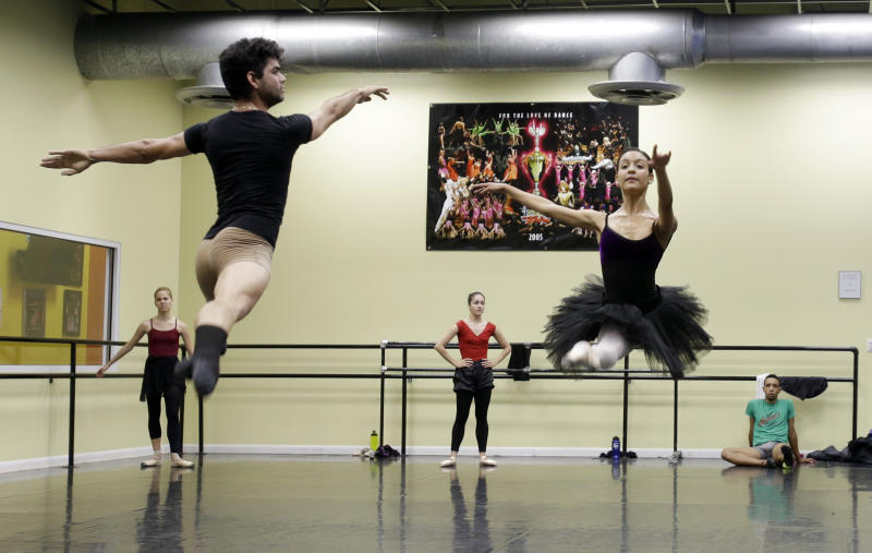 In this photo taken Friday, May 17, 2013, ballet dancers Edward Gonzalez, left, and Arianni Martin, right, practice in a dance studio in Miami. These dancers could be among the young talent of any ballet company, but for the moment they are something else: Immigrants in the United States trying to land dancing opportunities while navigating cultural differences and learning English. The ballerinas fled from the Cuban National Ballet while on tour in Mexico in April, and crossed the border into Texas. (AP Photo/Alan Diaz)