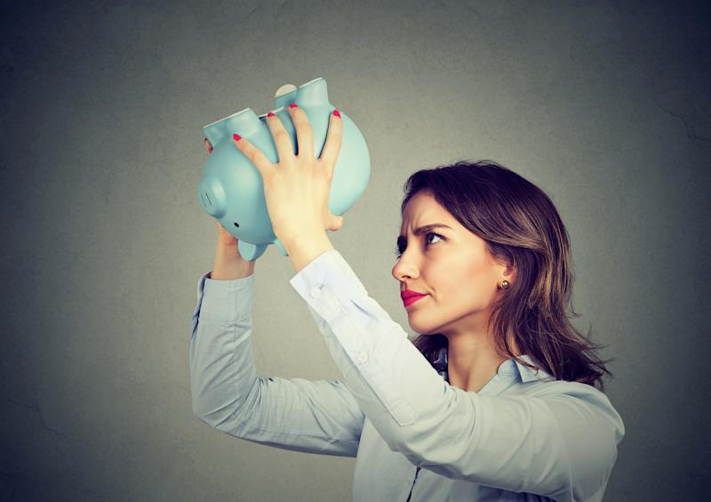 Person dismayed by an empty piggy bank.