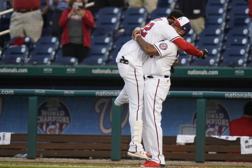 Washington Nationals' Juan Soto, left, celebrates with manager Dave Martinez after Soto hit a game-winning single in the ninth inning of an opening day baseball game against the Atlanta Braves at Nationals Park, Tuesday, April 6, 2021, in Washington. Victor Robles scored on the play, and Washington won 6-5. (AP Photo/Alex Brandon)