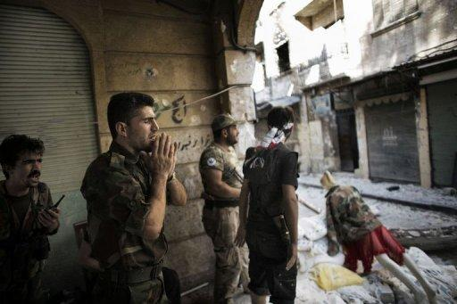 "A Free Syria Army fighter yells ""Allahu Akbar"" (God is Great) as he mans a position with his comrades only 50 meters away from a Syrian army post in the Old City of Aleppo September 16, 2012. At least 64 people died nationwide on Monday, including 36 civilians, 15 soldiers and 13 rebels, the Britain-based rights observatory said, after 148 were killed the previous day"