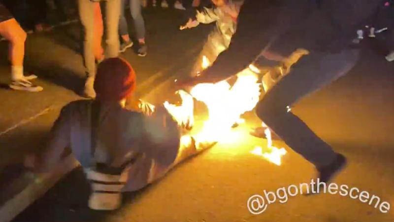 A man's legs are on fire as a witness tries to put it out.