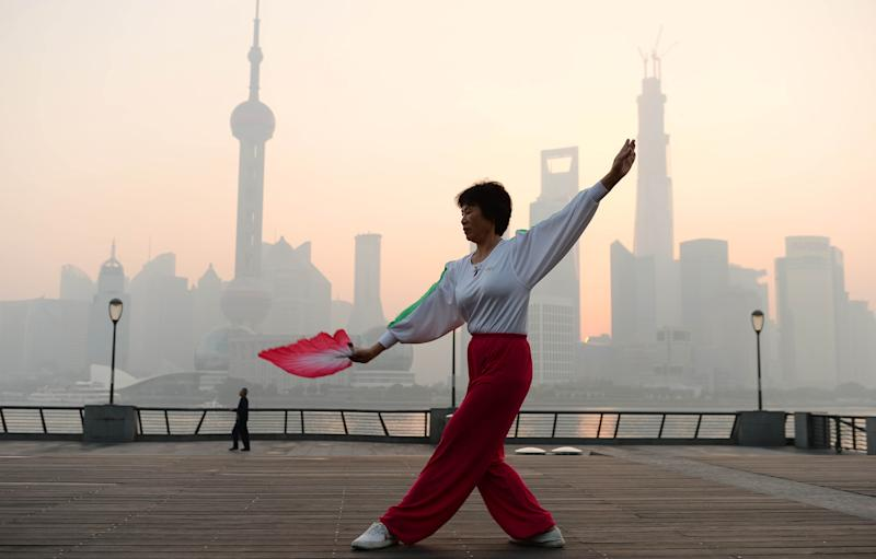 SHANGHAI, CHINA - NOVEMBER 07: (CHINA OUT) A woman does morning exercises at the Bund as heavy smog engulfs the city on November 7, 2013 in Shanghai, China. People were advised to stay indoors today as the Shanghai Environment Agency measured air pollution levels at five out of a possible six. (Photo by ChinaFotoPress/ChinaFotoPress via Getty Images)