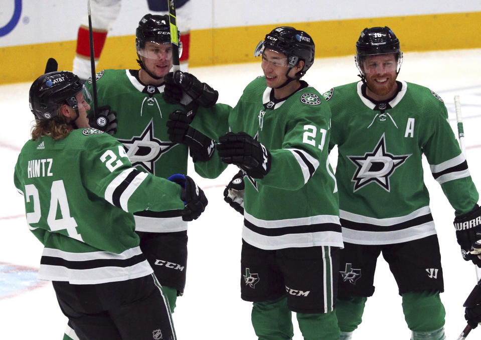 The Dallas Stars including left wing Roope Hintz (24), defenseman Miro Heiskanen (4), left wing Jason Robertson (21), and center Joe Pavelski (16) celebrate a goal against the Florida Panthers in the first period of an NHL hockey game on Sunday, March 28, 2021, in Dallas. (AP Photo/Richard W. Rodriguez)