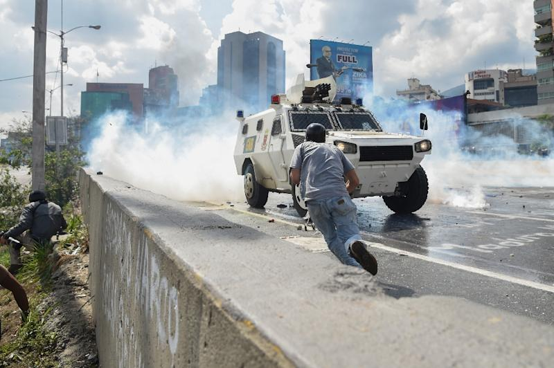 Demonstrators scatter as a National Guard riot control vehicle charges during a protest in Caracas, on May 10, 2017