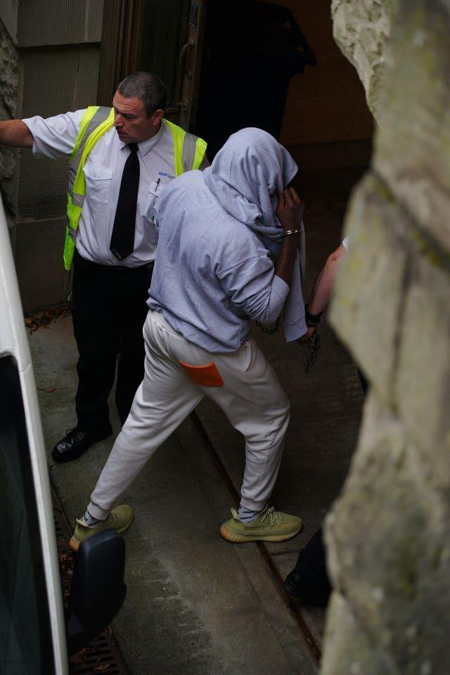 A man, believed to be co-defendant Louis Saha Matturie, gets out of a prison van at Chester Crown Court