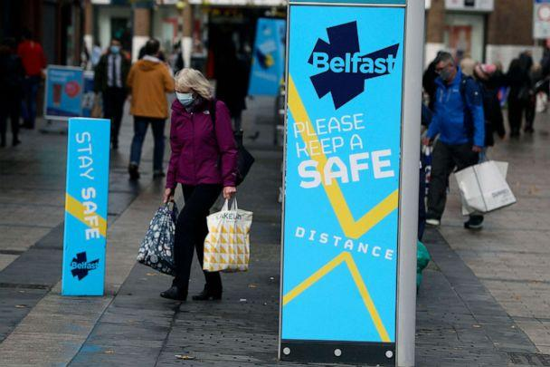 PHOTO: In this Oct. 14, 2020, file photo, a woman wears a face mask in central Belfast as Northern Ireland introduced the tightest COVID-19 restrictions in the United Kingdom, closing schools for two weeks and pubs and restaurants for a month. (Brian Lawless/AP, File)
