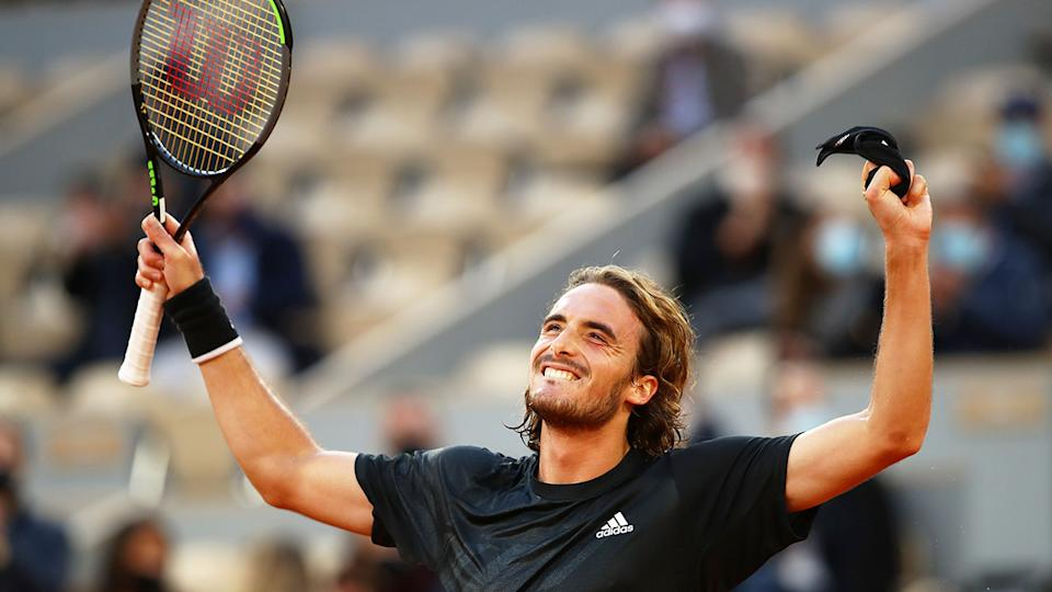 Seen here, Tsitsipas throws his arms up in triumph after his French Open quarter-final.