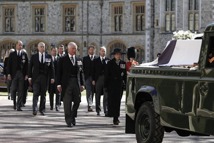 Members of the royal family walk behind Prince Philip's coffin resting in a modified Land Rover in a procession.