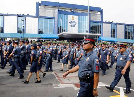 Policemen walk past Philippine National Police headquarters after taking part in the founding anniversary of the Philippine National Police celebration at Camp Crame in Quezon city Metro Manila, Philippines