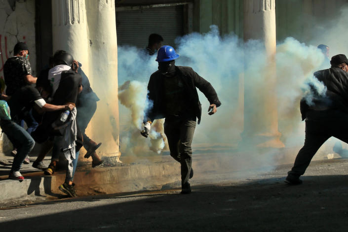 An anti-government protester runs with a tear gas canister fired by police during clashes in Baghdad, Iraq, Nov. 22, 2019. (Photo: Hadi Mizban/AP)