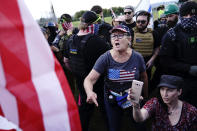 A right-wing demonstrator, center, yells at a counter protester to leave a rally by members of the Proud Boys and other right-wing demonstrators on Saturday, Sept. 26, 2020, in Portland, Ore. (AP Photo/John Locher)