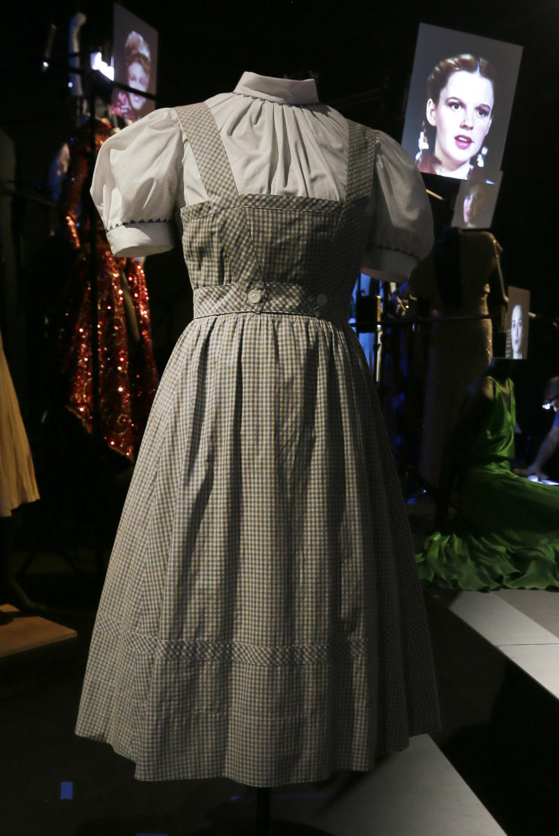 "In this Tuesday, Oct. 16, 2012 photo, the blue-and-white gingham pinafore dress worn by Judy Garland in her iconic role of Dorothy designed by Adrian for the 1939 film ""The Wizard Of Oz,"" with a video portrait of garland in the background, appears on display at the Hollywood Costume exhibition at the Victoria and Albert museum in London. On Sunday, Nov. 11, 2012, auction house Julien's Auctions said the gingham dress fetched the highest price of any item during a two-day auction of Hollywood memorabilia that attracted bids from around the world, selling for $480,000. (AP Photo/Alastair Grant)"