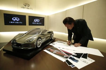 File photo of Infiniti chief designer Albaisa drawing a sketch of a car next to a quarter sized model of the Infiniti Emerg E car at Nissan Technical Center in Atsugi
