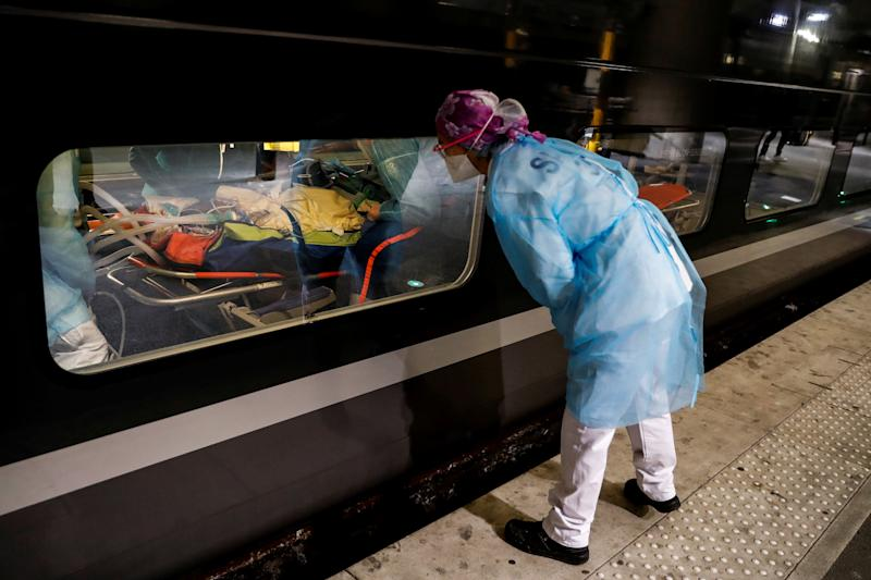 A medic looks through the window of a train before its departure to evacuate patients infected with the COVID-19. (Thomas Samson/Pool via REUTERS)